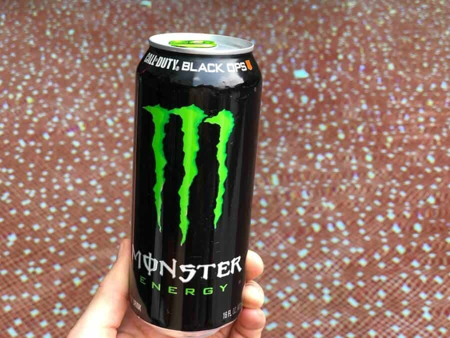 a can of monster energy drink in a persons hand with a tiled background
