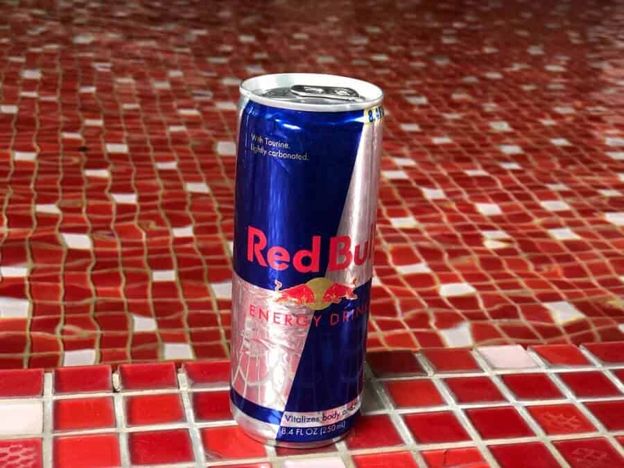 a can of blue and white Red Bull energy drink on an orange tiled surface