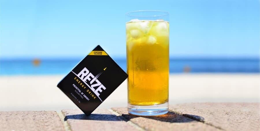a box of REIZE energy drink rested on a tilted angle against a glass of an iced yellowish beverage against a beachlike background