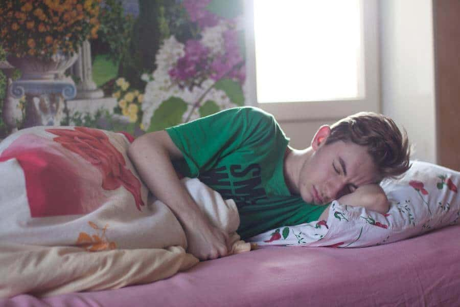 A young man lying on his side in bed feeling unwell