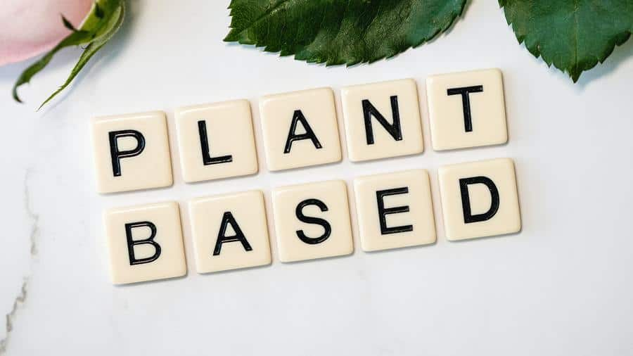 Scrabble-like tiles on a marble surface spelling out Plant Based with green leaves at the top.
