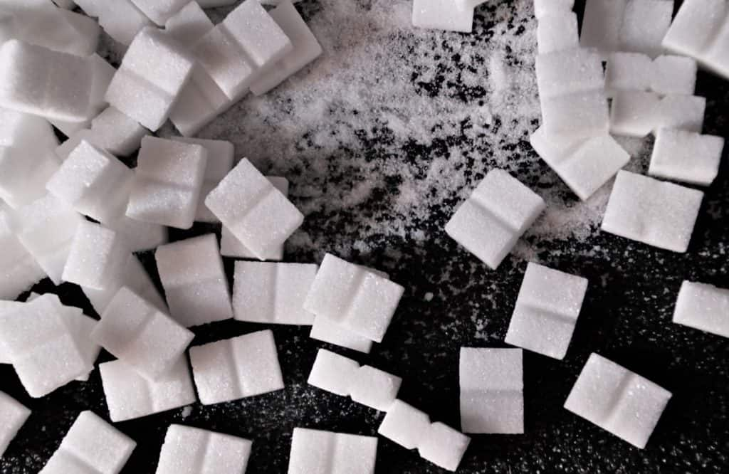 Sugar cubes and sugar on black surface.