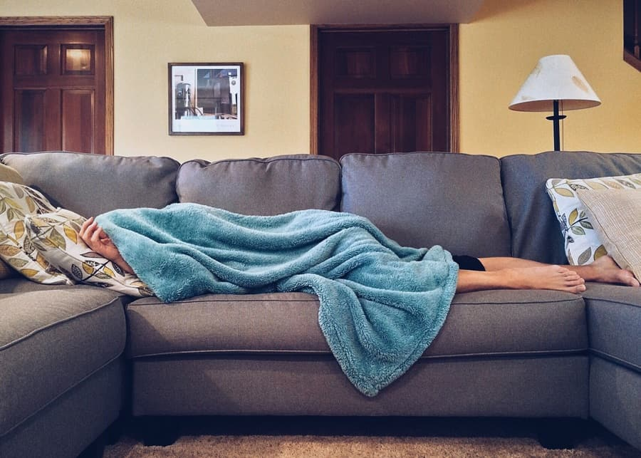 Person lying on a couch with a blanket over their head as if slightly ill.