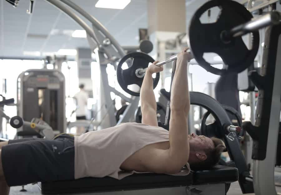 man in white tank doing a bench press in the gym