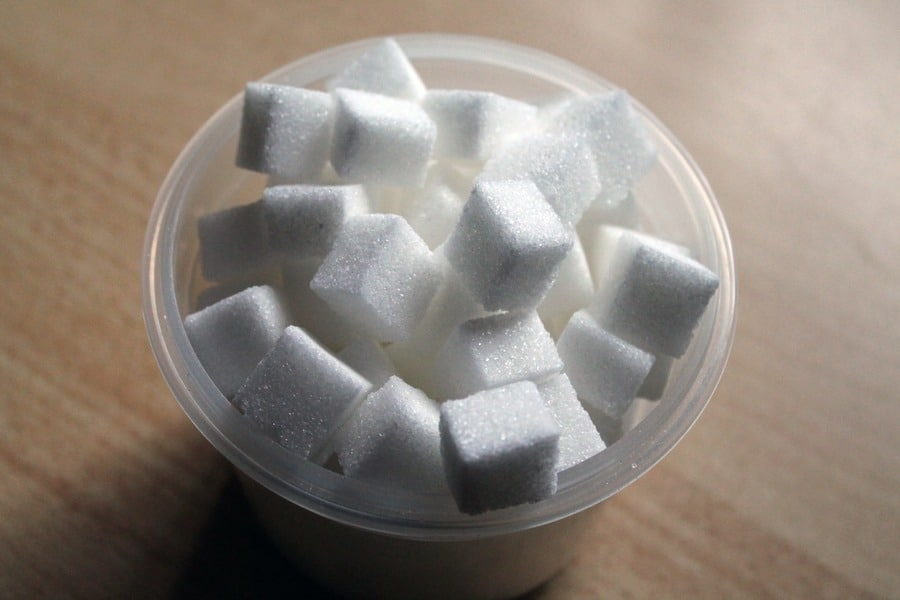 Sugar cubes in a small plastic bowl.