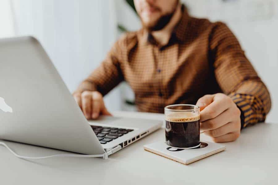 guy working on a laptop holding a cup of coffee.