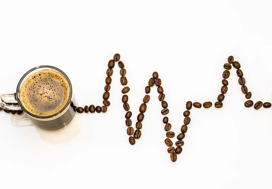 A cup of coffee and coffee beans arranged in a heart rhythm monitor.