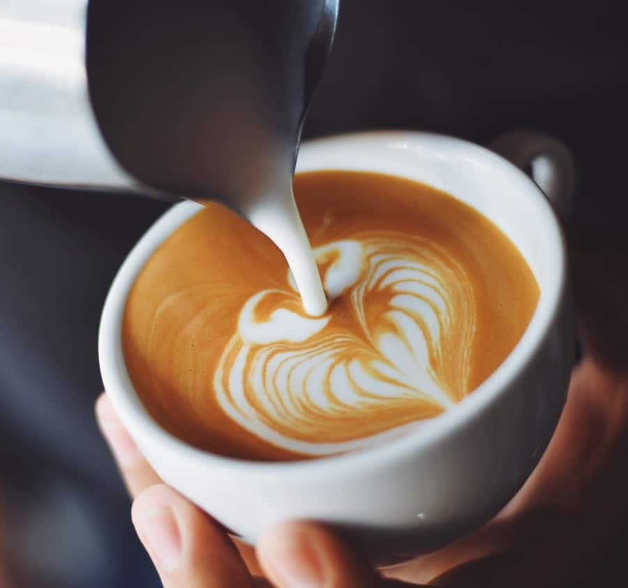 Milk being poured into a cup of coffee forming latte art
