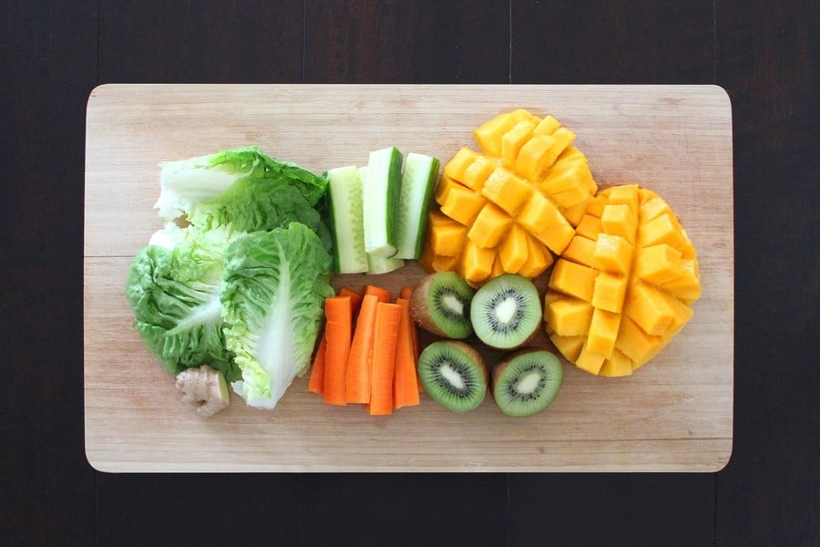 vegetables and fruits on a wooden chopping board