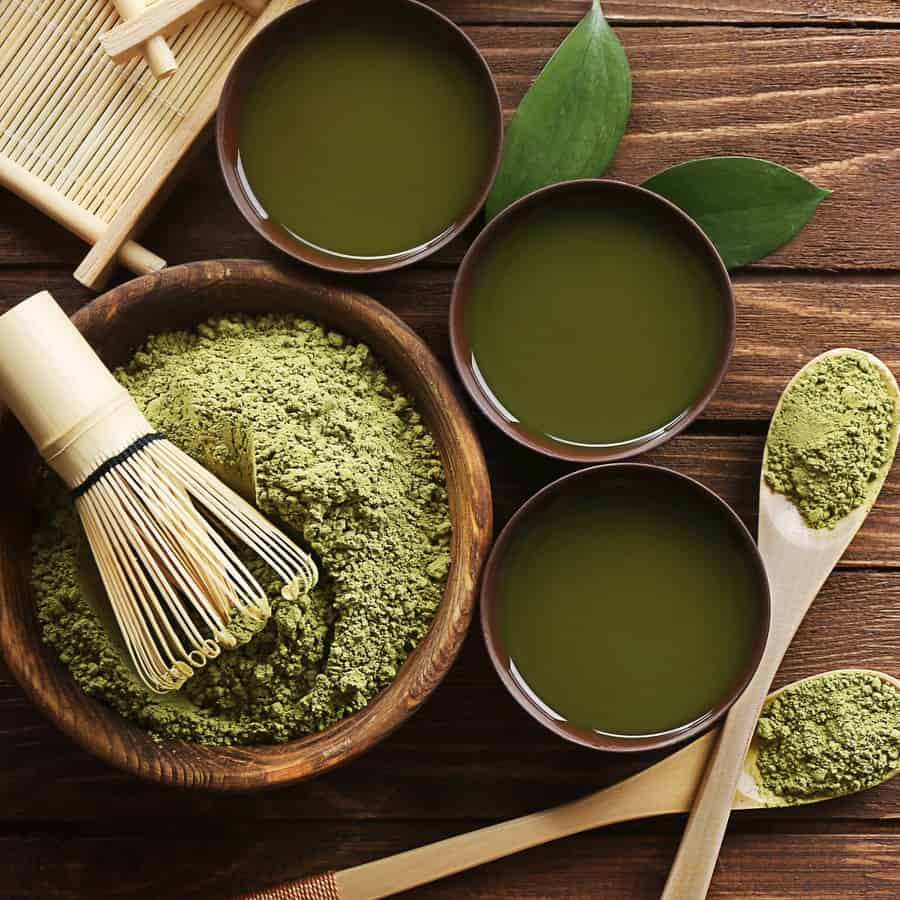 Green tea powder in a bowl along with green tea cups and spoons full of green tea.