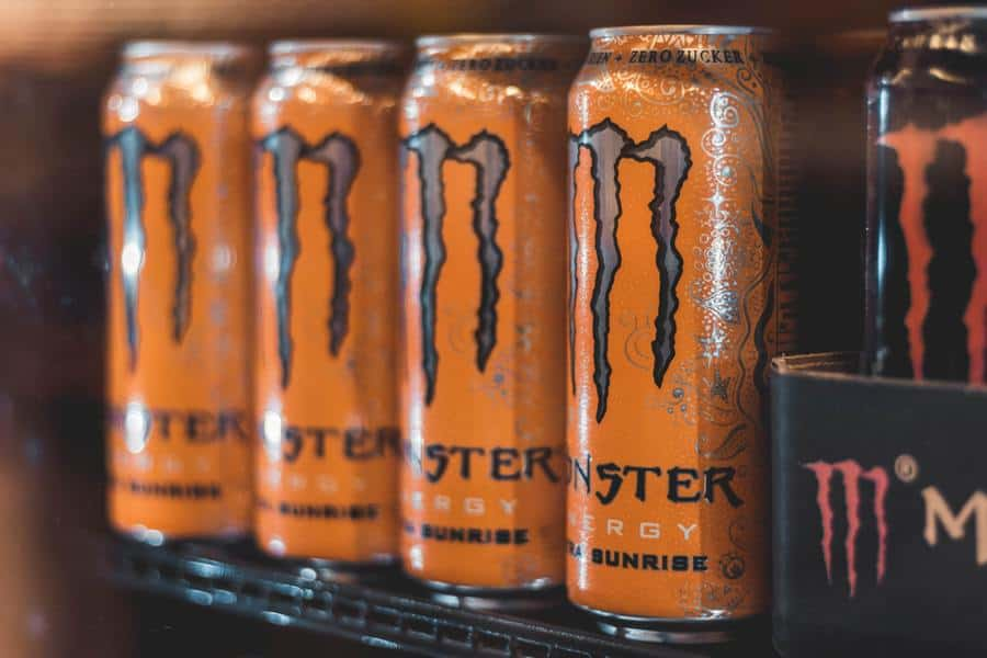 Monster energy drinks lined up on a shelf.