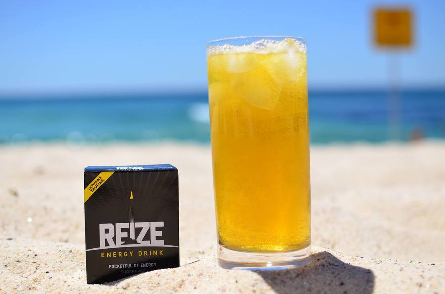 Glass of REIZE with its packet to the side on a sandy beach.