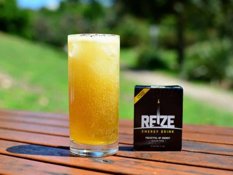 Glassful of REIZE energy drink next to its packaging.