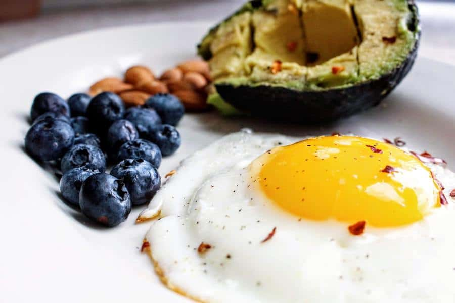 A fried egg with a side ofo blueberries, nuts and half an avocado on a plate