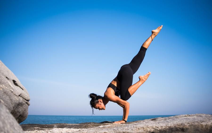 Woman balancing upside down on the ground.