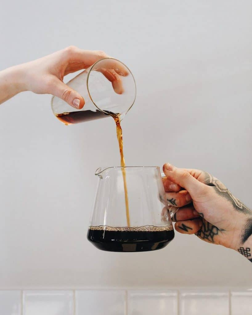 glass of coffee being poured into a small jug