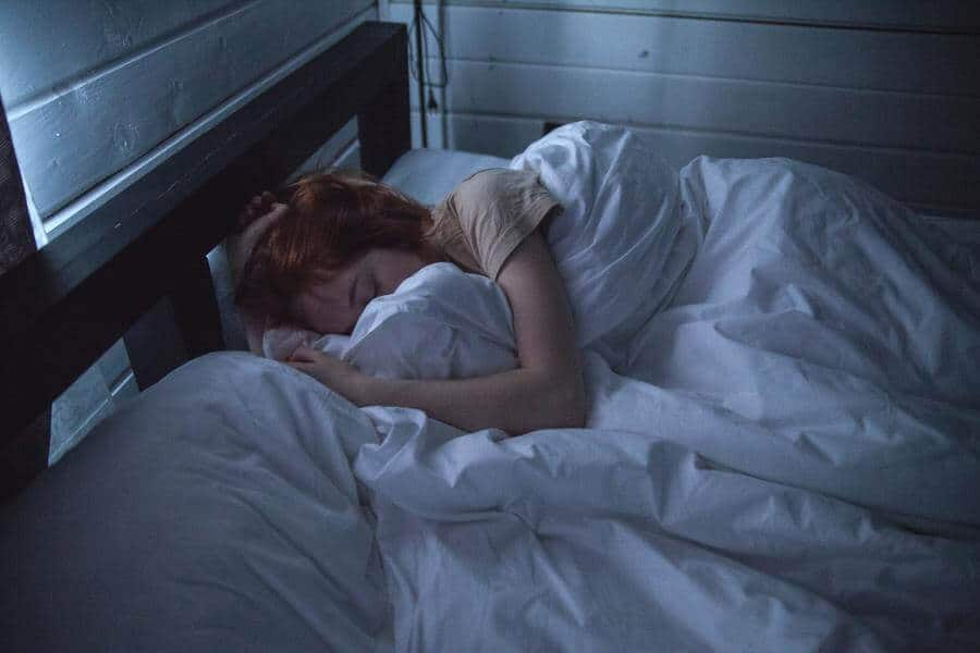 Woman sleeping in bed under white covers.