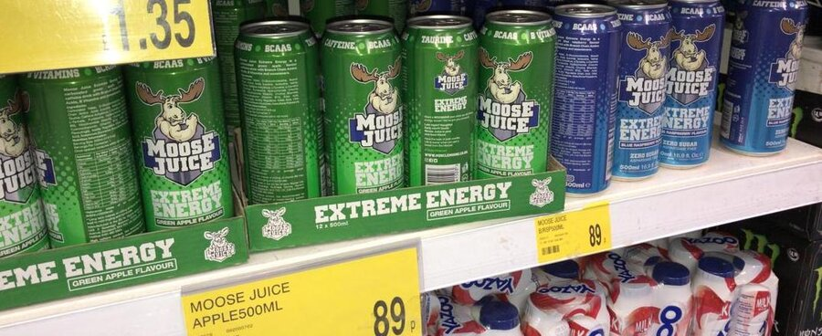 A lot of different Moose Juice energy drink cans on the shelf in a supermarket in the UK
