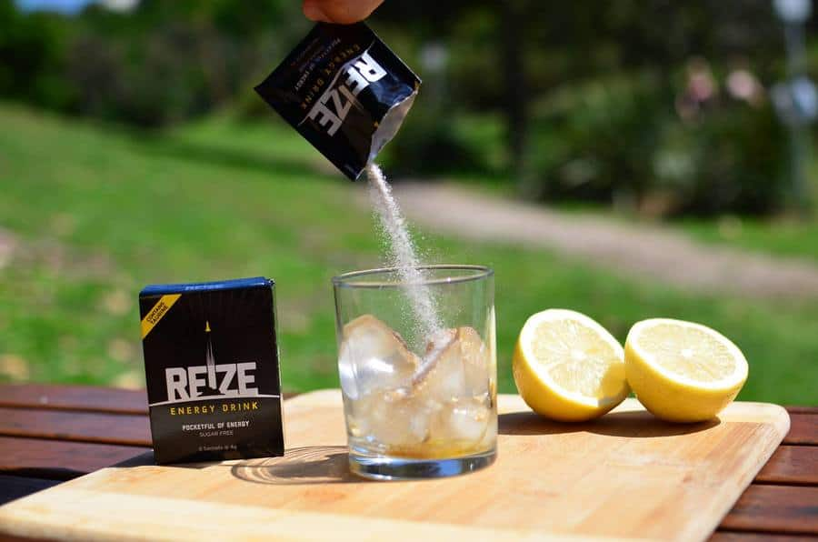 REIZE powder poured into a glass of ice with lemons in the background.