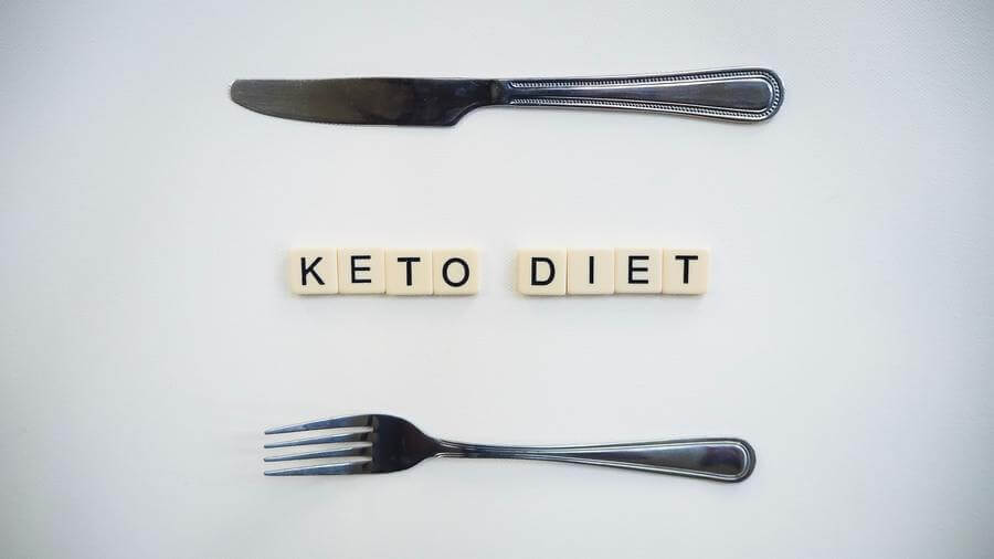 Scrabble tiles spelling out keto diet arranged between a fork and knife.