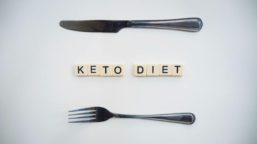 Keto Diet spelt out using scrabble tiles with a fork and knife.