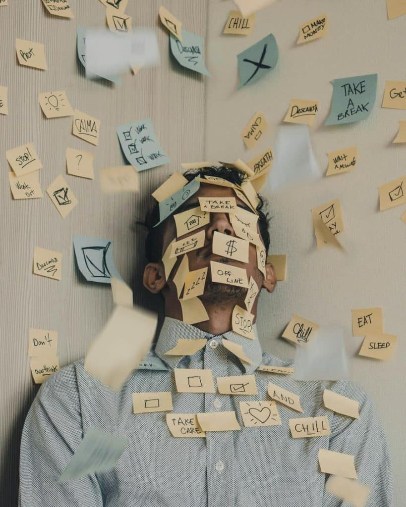 sticky notes all over the wall and on a guys face