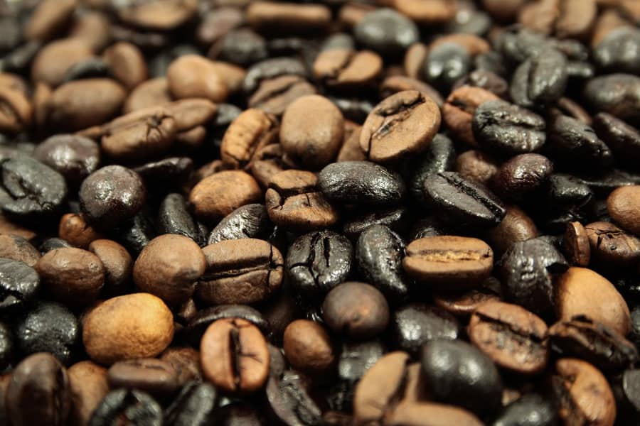 Brown and black coffee beans piled together.