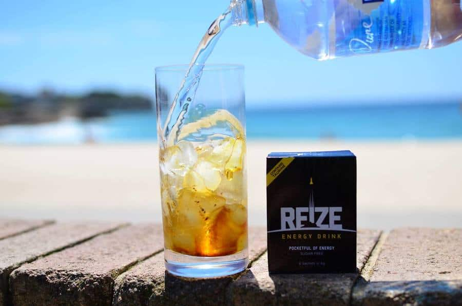 Water being poured into a glass of REIZE energy drink.