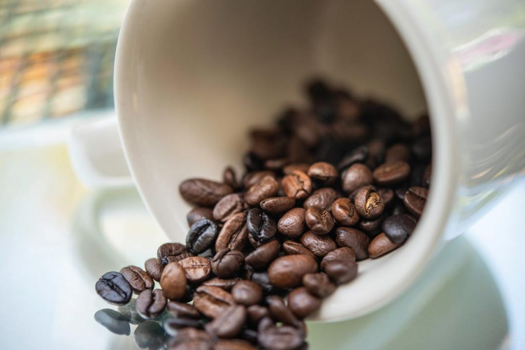 Coffee beans spilling from a mug.
