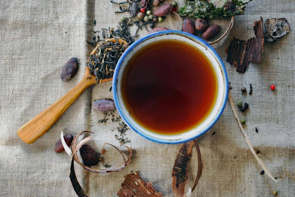 A picture of black tea with herbs surrounding the mug
