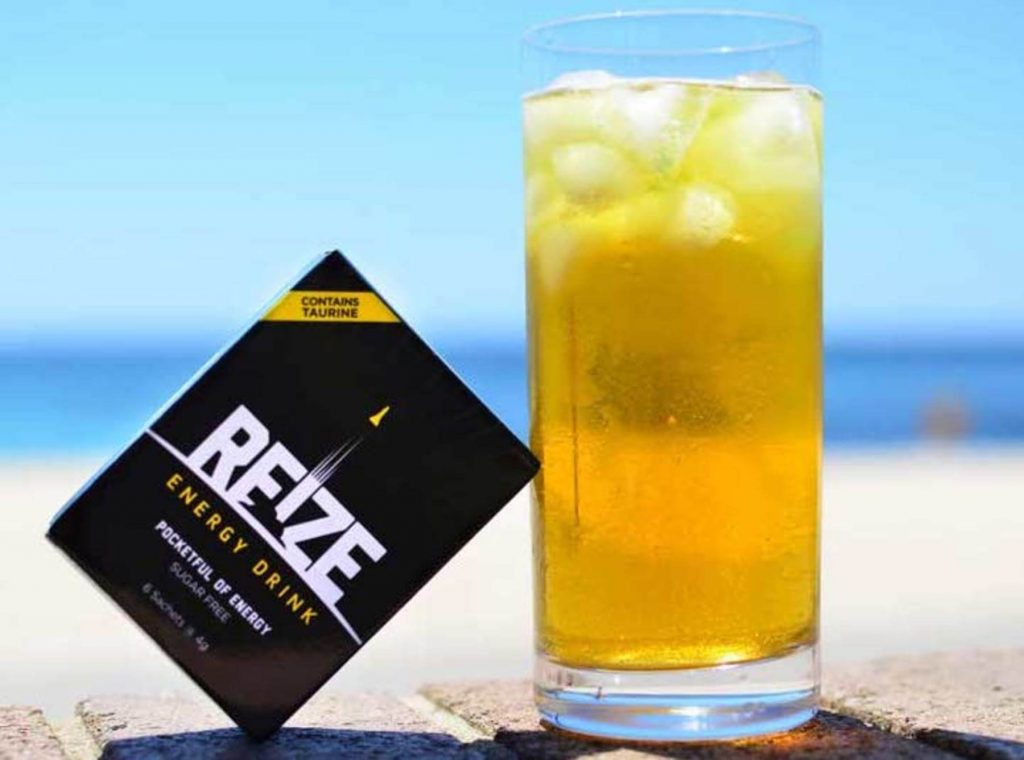 A glass of REIZE is on the beach with a sachet of REIZE leaning against it.