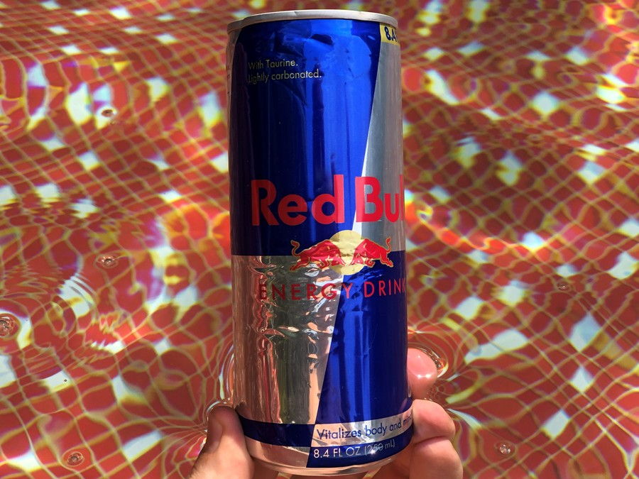 A hand holding a can of Red Bull.
