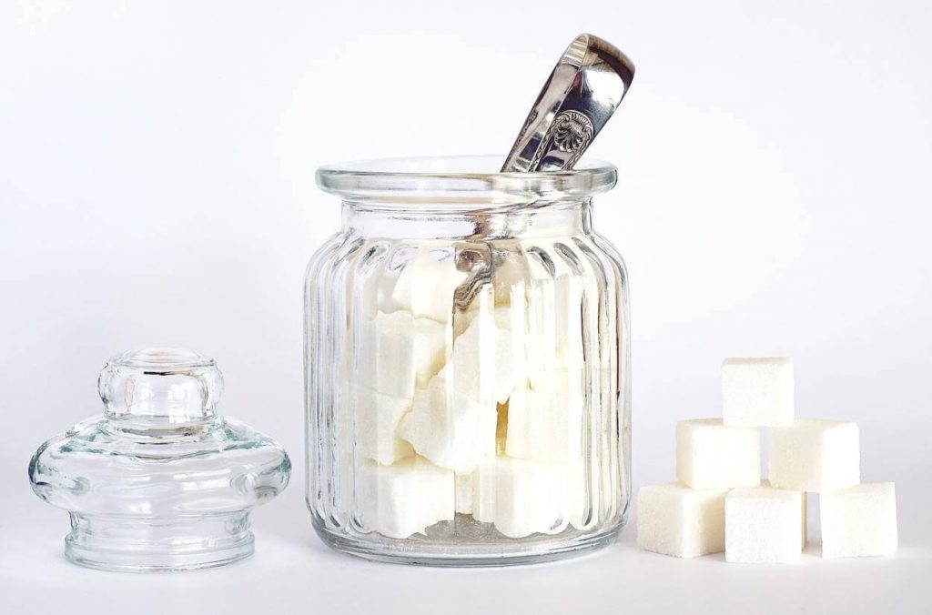 A picture of sugar cubes in a glass jar