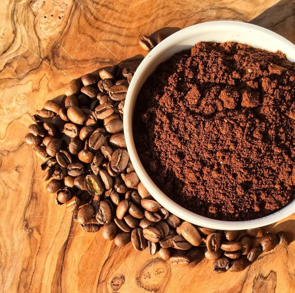 A white bowl contains caffeine powder while being surrounded by coffee beans on a table.