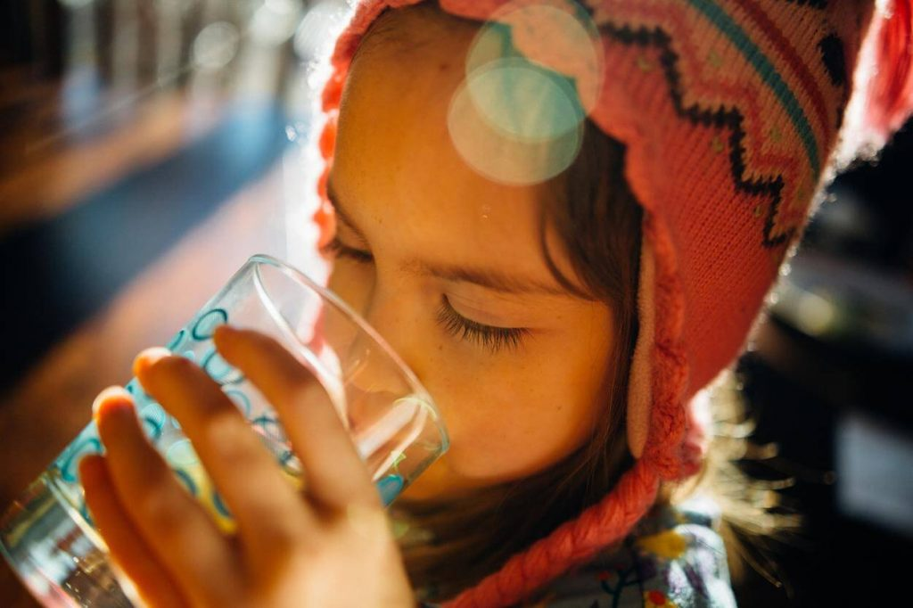 A little girl is drinking a glass of water.