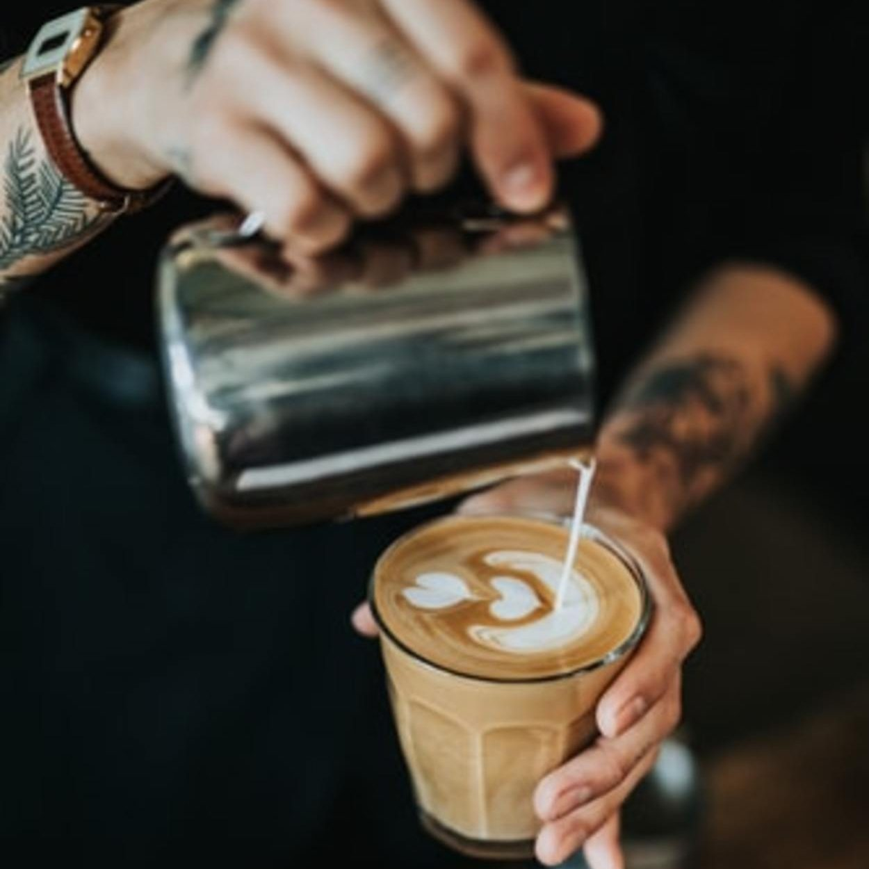 A barista pouring coffee in a cup.