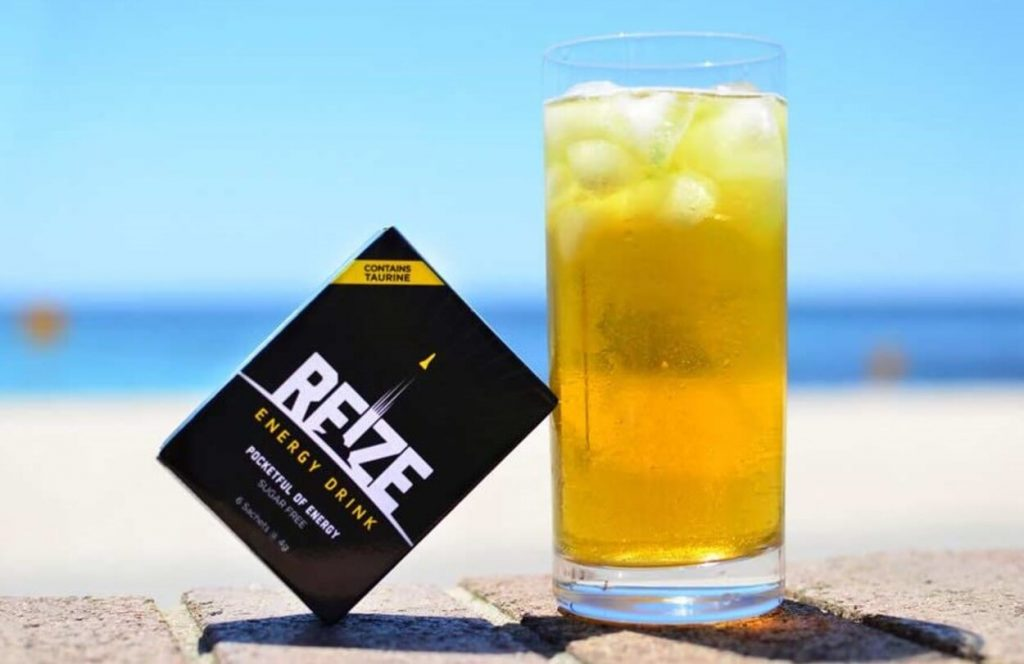 A glass of REIZE with a sachet of REIZE in front of the beach.