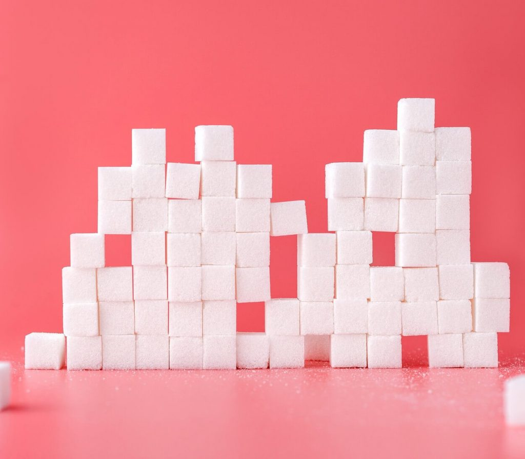 Sugar cubes stacked atop each other against a vibrant red background.