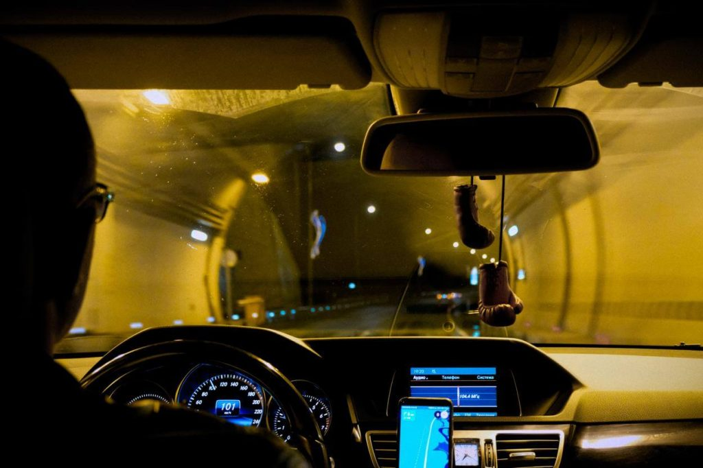 A picture of a man driving at night
