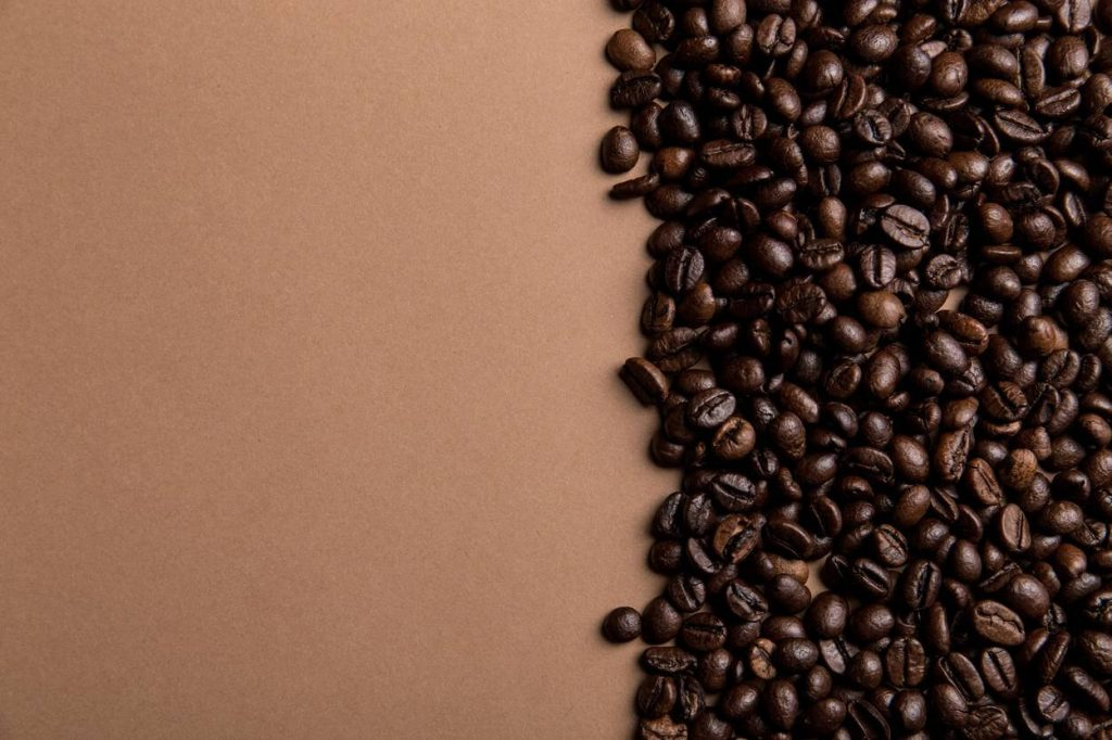 Coffee beans at one side of a brown background.