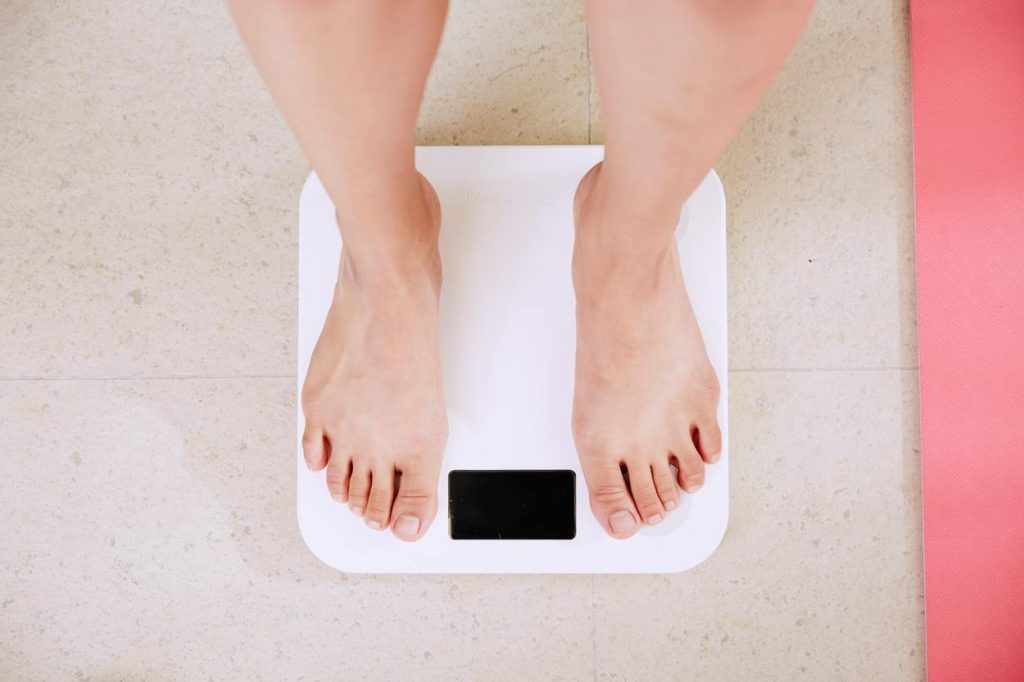 A woman stands on a weighing scale.