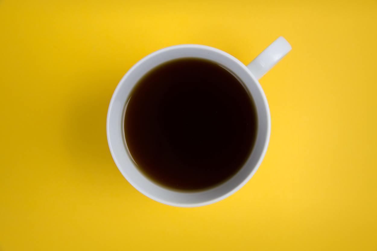 A cup of coffee against yellow background.