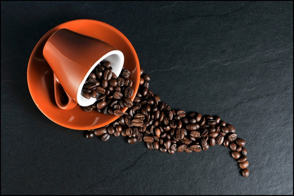 Coffee beans spilling from cup.