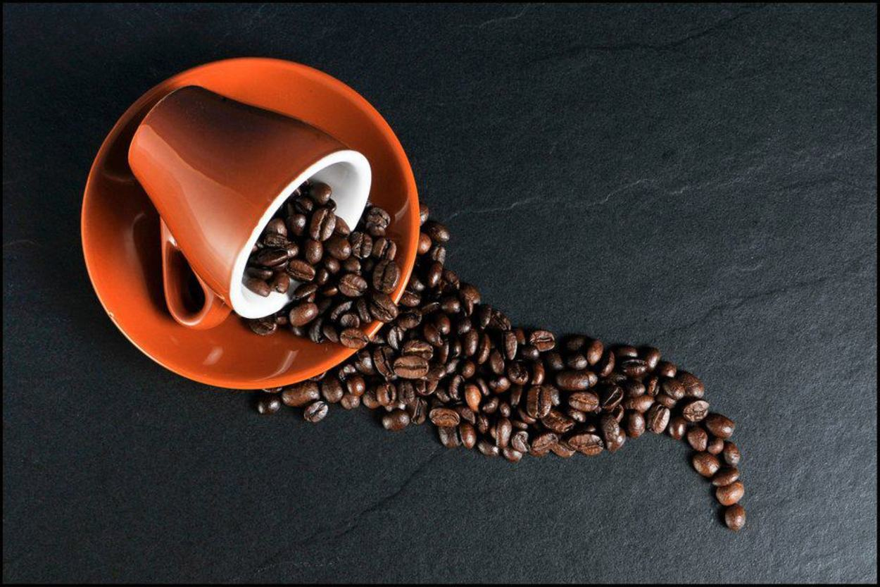 Coffee Beans pouring out of  a cup.