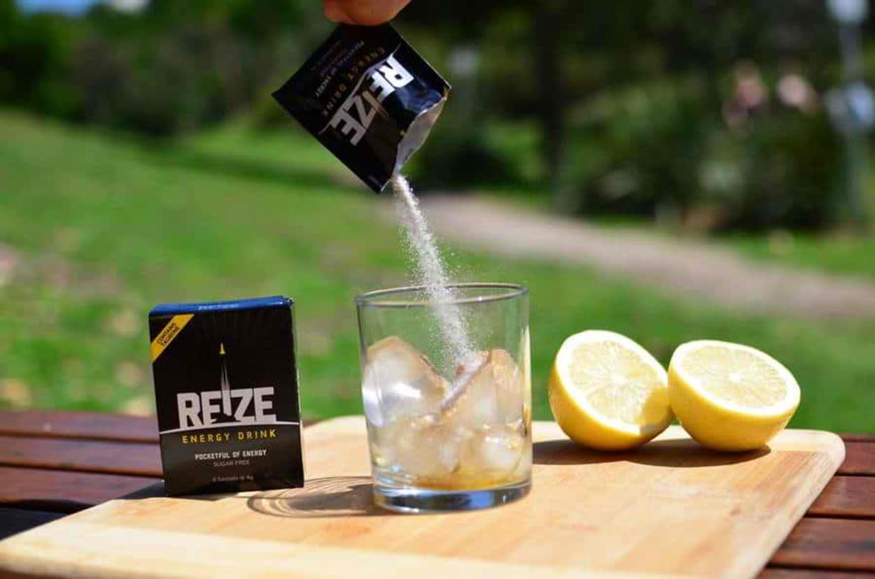 A sachet of REIZE Energy drink poured into a glass full of ice. A packet of REIZE energy drink and a lemon sliced in half can also be seen in the background.
