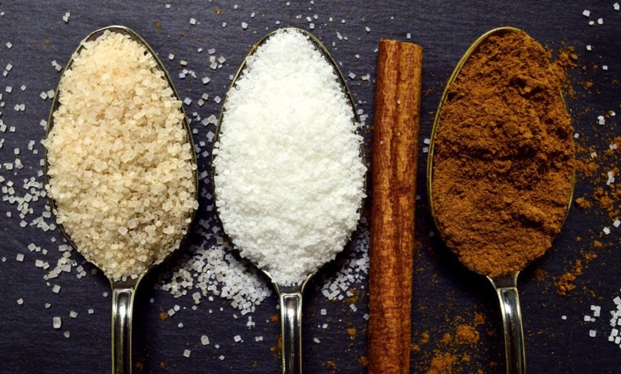 Three spoons with three different types of sugar.