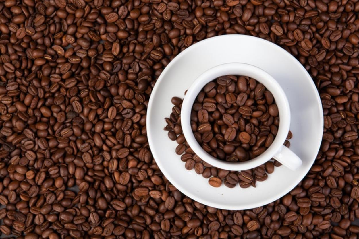 A cup of coffee surrounded by coffee beans.