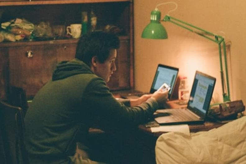 A man sitting in front of two laptop.