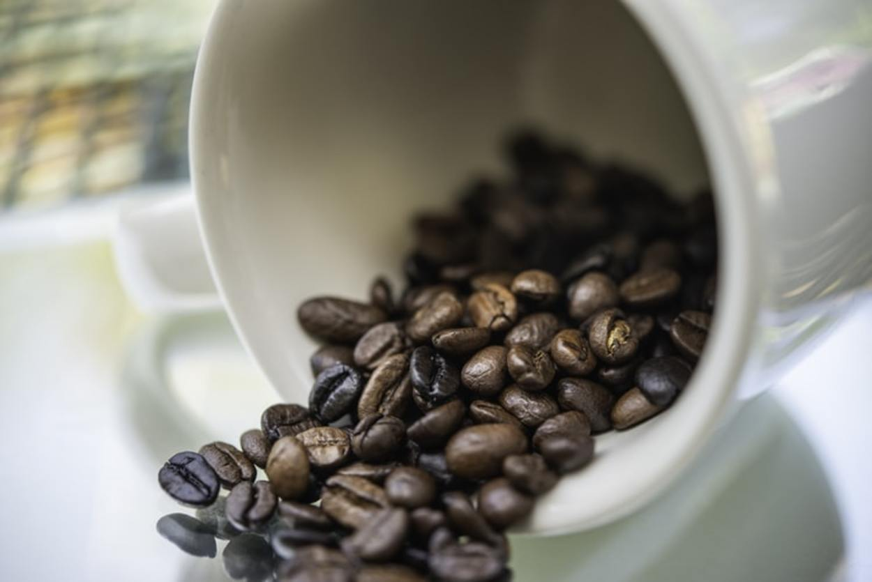 Coffee beans spilling out of a cup.