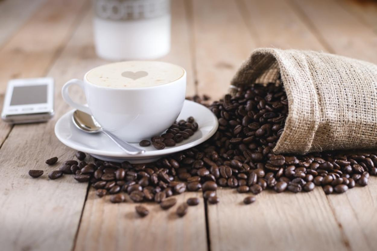 A cup of coffee on coffee beans.
